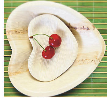 Heart shaped palm leaf plates holding two cherries